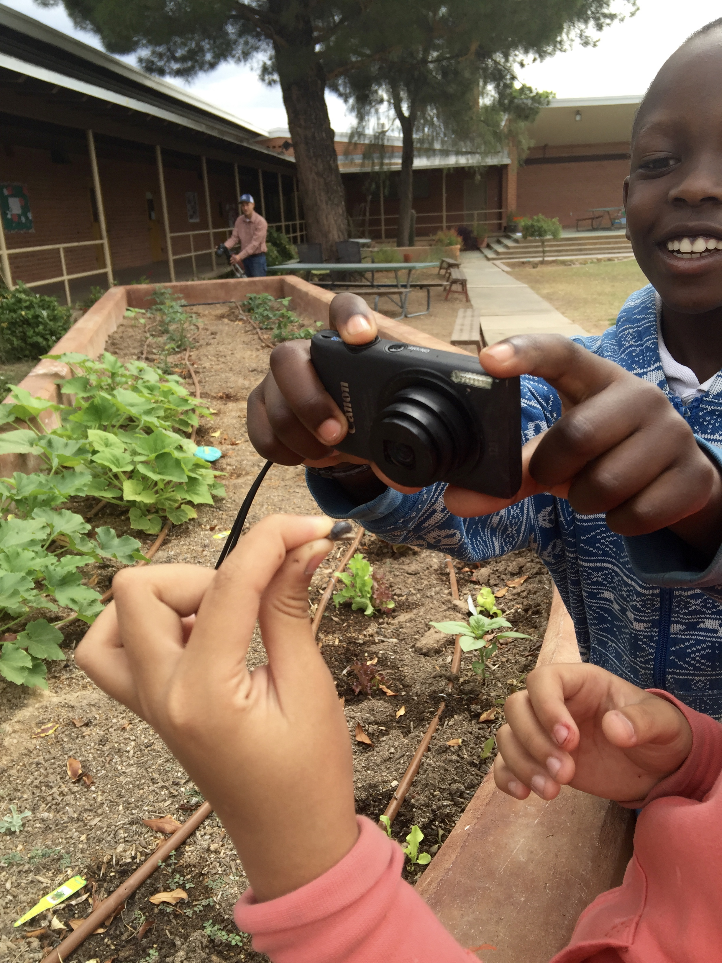 Image of a elementary-aged student taking a photo of a worm that another young student is holding