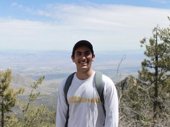 Aaron Nach standing in front of trees and mountains