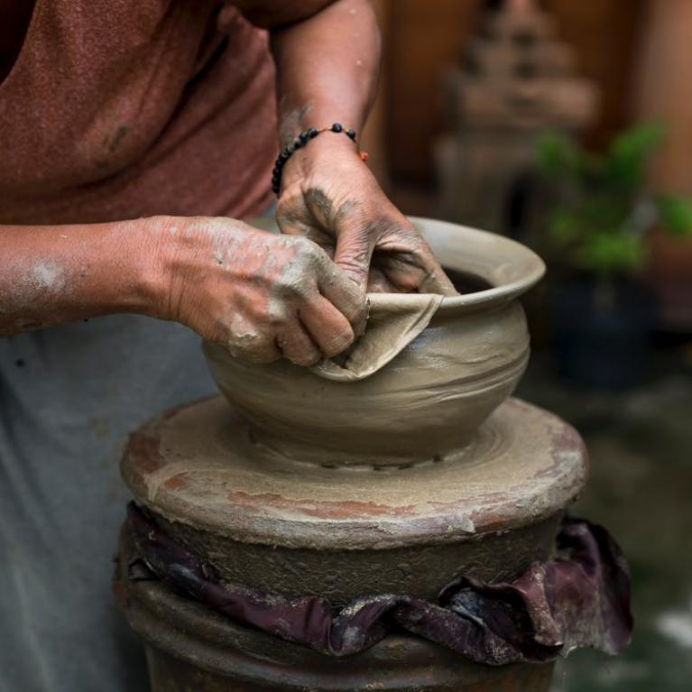 person sculpting a bowl out of clay